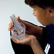 Boy using thermometer to measure hand temperture, ice water temperature.
