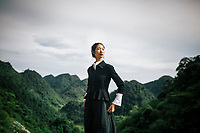 A young Asian woman in a simple black jacket overlooking an epic mountain landscape in Mai Chau, northern Vietnam.