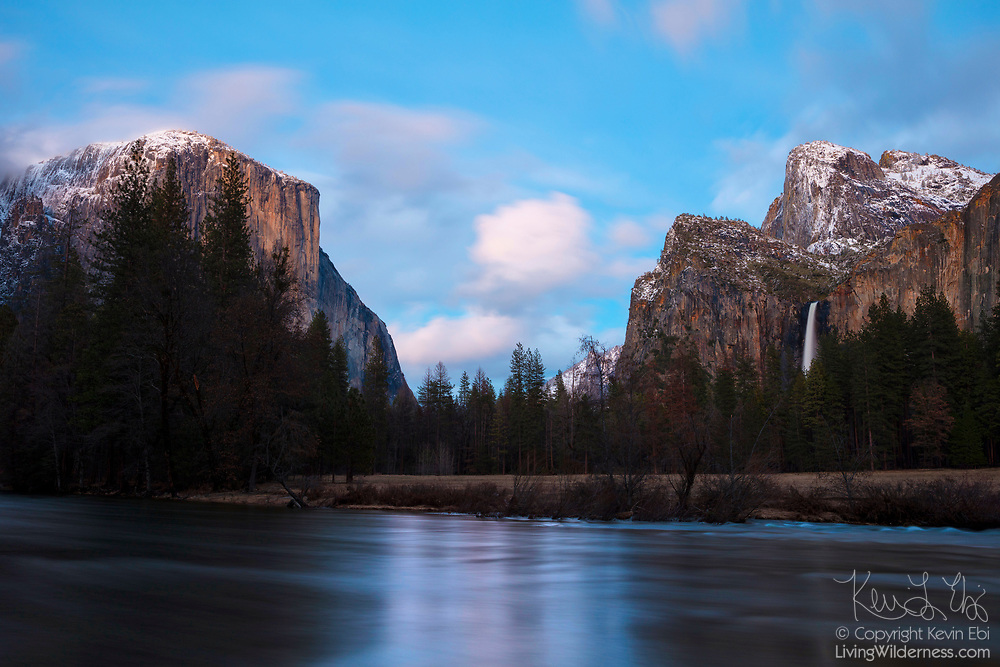 The Gates of the Valley stand tall over the Merced River at Valley View in Yosemite National Park, California. At left is El Capitan, a 7,573-foot (2,308 meter) sheer granite peak. At right is Bridalveil Fall, a 620-foot (189-meter) waterfall.