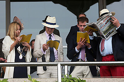 Racegoers check the form at a wet and windy opening day of Glorious Goodwood in the UK, Tuesday, 30th July 2013 <br /> Picture by Stephen Lock / i-Images