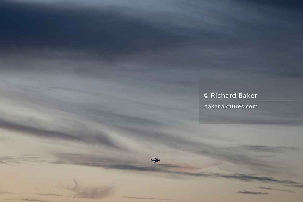 The silhouette of an airliner that has taken off from Heathrow Airport to the west, and overflying the capital amid high altitude soft clouds in a dusk sky over south London, on 24th August 2019, in London, England.