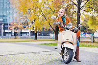 Portrait of beautiful woman talking on smartphone while waiting and  sitting on motorbike in park
