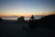 Caped woman greeting sunrise on Jekyll Island Beach