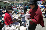 Orlando Ayme, 35, (wearing a red poncho), bargains with a vendor of flour and beans before he buys some. He sold two of his sheep at this weekly market in the indigenous community of Simiatug for $35 US in order to buy potatoes, grain and vegetables for his family.(Supporting image from the project Hungry Planet: What the World Eats.)