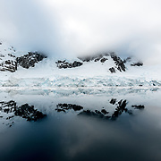 """Mountains on the shore of the Lemaire Channel are reflected on glass waters in the Lemaire Channel. The Lemaire Channel is sometimes referred to as """"Kodak Gap"""" in a nod to its famously scenic views."""