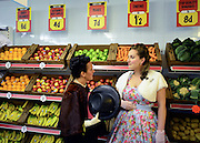 © Licensed to London News Pictures. 14/09/2012. Goodwood, UK Two women chat in the fruit and vegetable aisle. Tesco supermarket has recreated a sixties style branch of one of it's stores at The Goodwood Revival. Customers can browse items from the period and the staff are all wearing vintage uniform. People enjoy the atmosphere at the 2012 Goodwood Revival. The event recreates the glorious days of motor racing and participants are encouraged to dress in period dress. Photo credit : Stephen Simpson/LNP