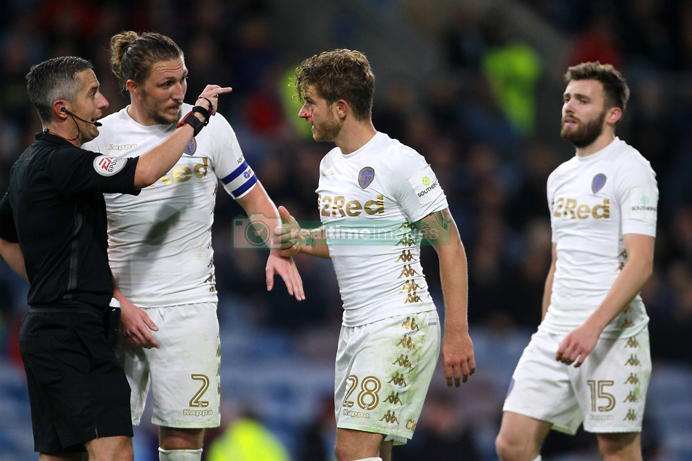 Leeds United's Gaetano Berardi (centre) speaks with referee Darren Bond as he is sent off the pitch with a cut on his eye during the Carabao Cup, third round match at Turf Moor, Burnley.