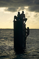 a group of young people sit on pier after swimming in Vieques, Puerto Rico