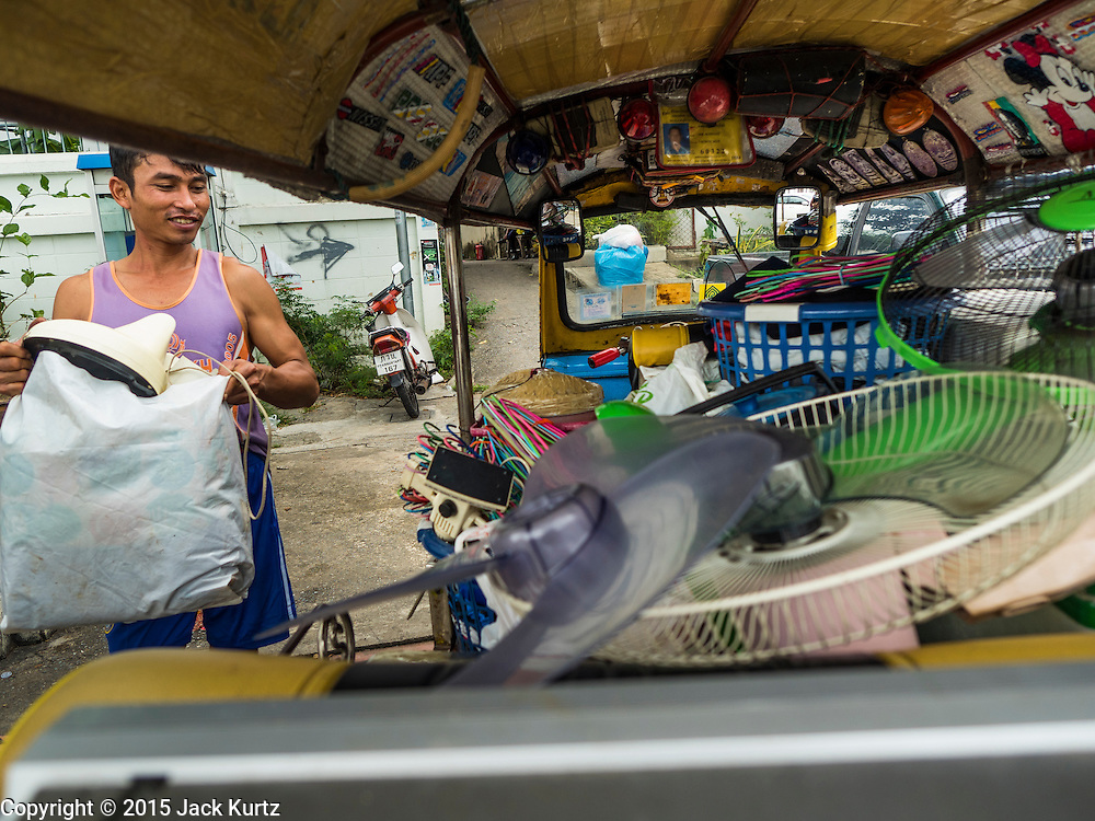 05 OCTOBER 2015 - BANGKOK, THAILAND:  A man packs his belongings into a tuk-tuk (three wheeled taxi) on the day he was evicted from the Wat Kalayanamit neighborhood. Fifty-four homes around Wat Kalayanamit, a historic Buddhist temple on the Chao Phraya River in the Thonburi section of Bangkok, are being razed and the residents evicted to make way for new development at the temple. The abbot of the temple said he was evicting the residents, who have lived on the temple grounds for generations, because their homes are unsafe and because he wants to improve the temple grounds. The evictions are a part of a Bangkok trend, especially along the Chao Phraya River and BTS light rail lines. Low income people are being evicted from their long time homes to make way for urban renewal.        PHOTO BY JACK KURTZ