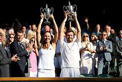 Alexander Peya and Nicole Melichar with their winners trophies after the Mixed doubles final on day thirteen of the Wimbledon Championships at the All England Lawn Tennis and Croquet Club, Wimbledon. PRESS ASSOCIATION Photo. Picture date: Sunday July 15, 2018. See PA story TENNIS Wimbledon. Photo credit should read: Nigel French/PA Wire. RESTRICTIONS: Editorial use only. No commercial use without prior written consent of the AELTC. Still image use only - no moving images to emulate broadcast. No superimposing or removal of sponsor/ad logos. Call +44 (0)1158 447447 for further information.