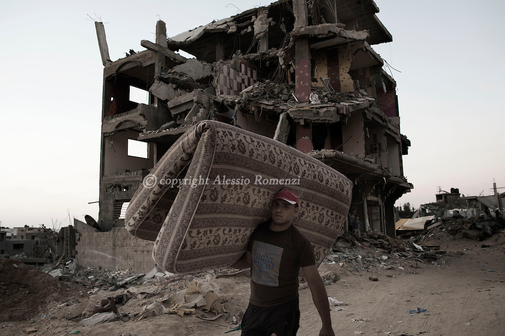 Gaza Strip, Gaza City: A Palestinian man is seen as he carries a mattress in Al Shaaf neighbourhood during a 72 hours ceasefire on August 11, 2012. ALESSIO ROMENZI
