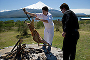Chef roasting lamb, Lake Llanquihue and Osorno Volcano, Chile..MODEL RELEASED