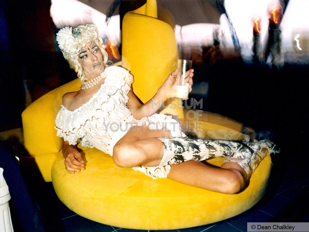 Transvestite lounging on a yellow sofa wearing Marilyn Monroe boots, Ibiza, 1999