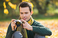 Young man watching photographs on digital camera in park during autumn