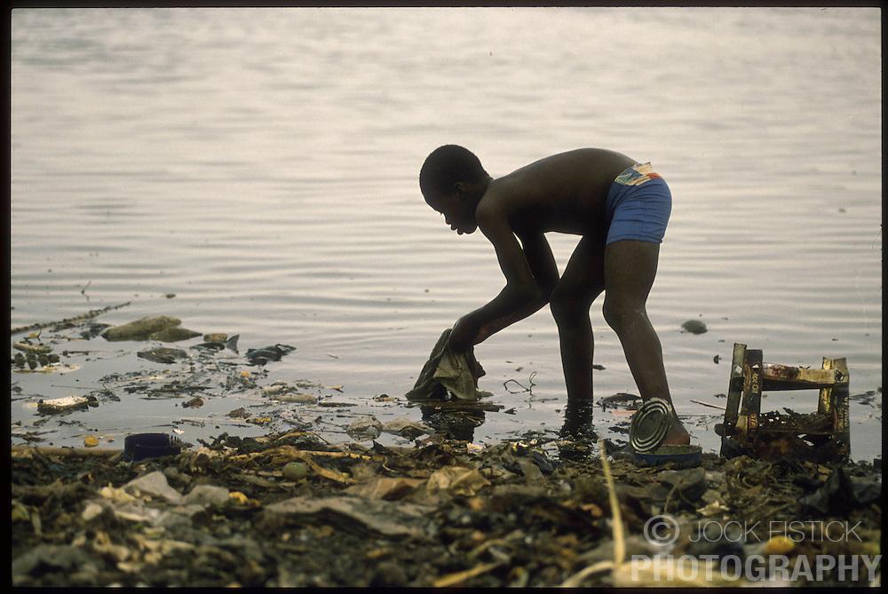 CAP HAITIEN, HAITI - A young boy scavenges for food in a trash dump. (PHOTO © JOCK FISTICK)....