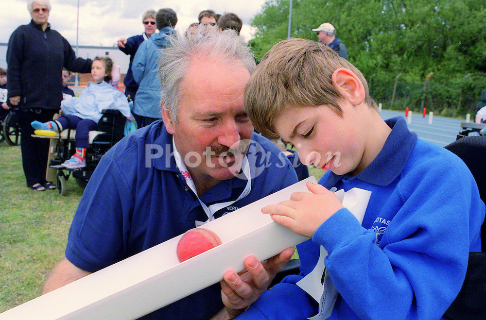 Coach and young boy with sensory impairments taking part in Mini games sports event held at Stoke Mandeville Stadium,