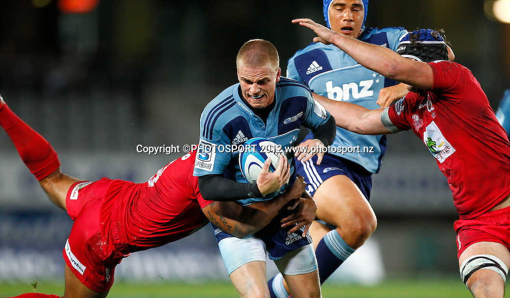 Gareth Anscombe of the Blues is tackled during the Super Rugby game between The Blues and The Reds at Eden Park, Auckland, New Zealand, Friday 27 April 2012. Photo: Simon Watts / photosport.co.nz