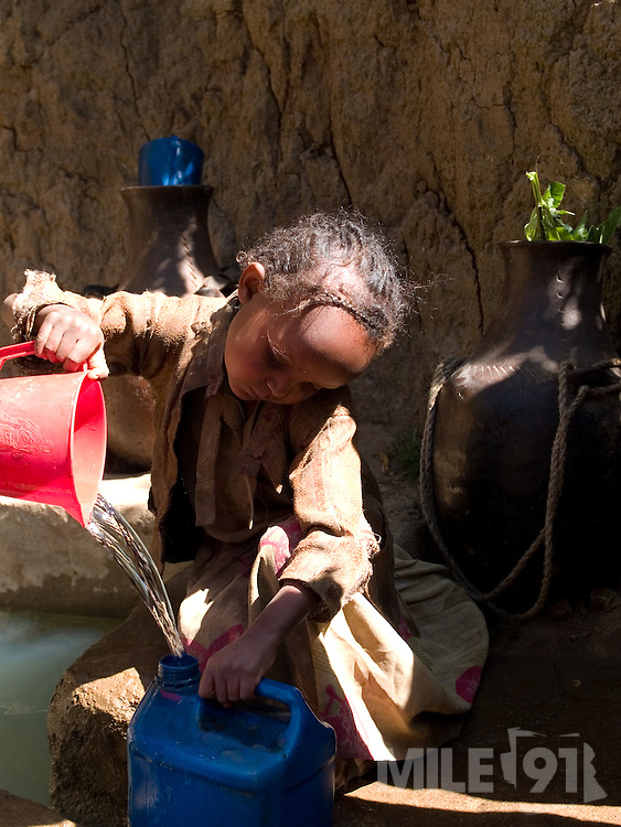 Children collecting water from a capped spring near their village in Kotoba, Ethiopia. Capping the spring has helped improve access and the quality of the water.