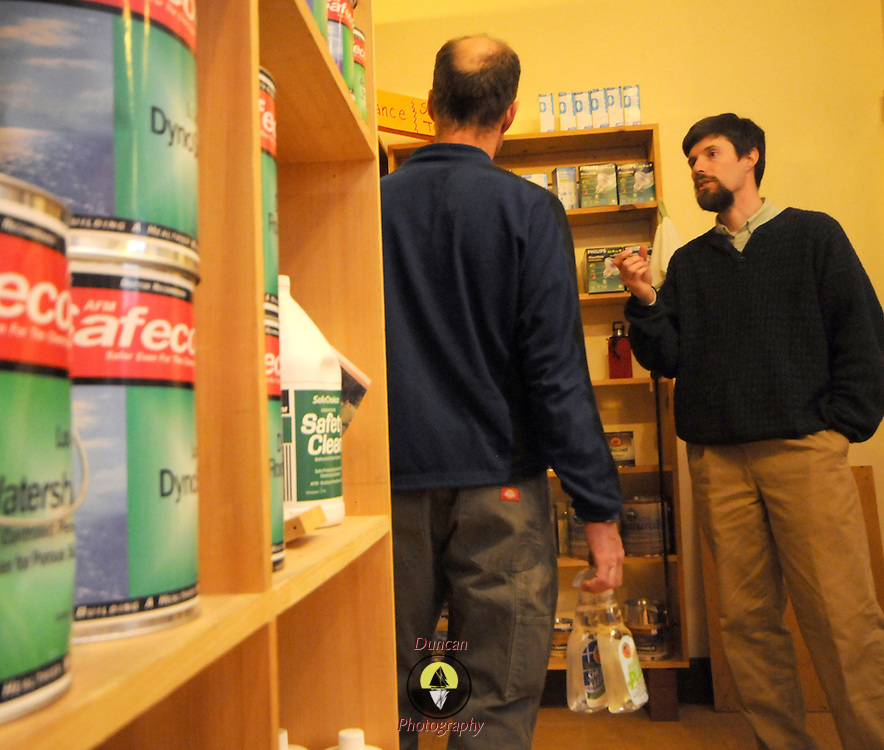 """4/5/11 -- BRUNSWICK, Maine.  Fred Horch, right, discusses paints which are less harmful to the air with a customer on Tuesday afternoon. Horch, the owner of the shop which bears his name on Maine St. in Brunswick, has decided to sell the environmentally friendly products store while he and his family travel to Japan for a year. Horch's wife, Hadley, is a professor at Bowdoin and will be on sabbatical. """"I'll miss the people more than anything here the store """" said Horch. He hopes to turn over the store to a new owner by June 1 and will be moving in July. Photo by Roger S. Duncan."""