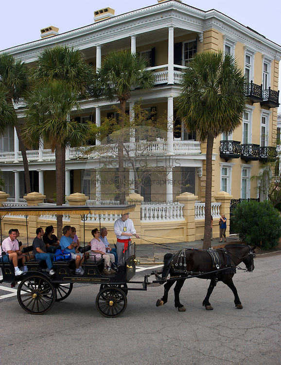 A horse drawn carriage tour passes a stately mansion along the historic Battery in Charleston, SC. Charleston founded in 1670 is considered America's most beautifully preserved architectural and historic city.