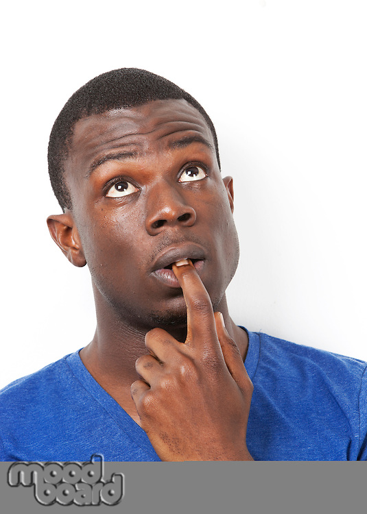 Pensive young African American man with finger in mouth against white background