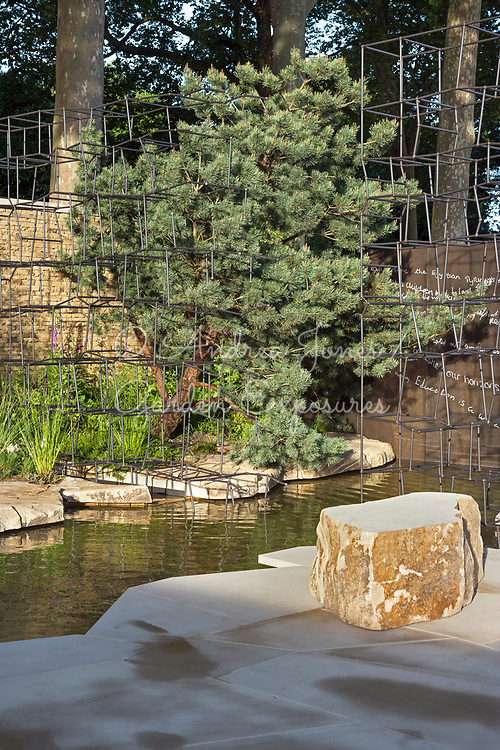Sculptural steel frame, bronze etched wall with text, water feature, pine tree and stone paving<br /> <br /> Breaking Ground <br /> <br /> Designed by<br /> Andrew Wilson and Gavin McWilliam<br /> <br /> Built by<br /> The Outdoor Room<br /> <br /> Sponsored by<br /> Darwin Property Investment Management Ltd