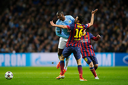 Barcelona Midfielder Sergio Busquets (ESP) is challenged by Man City Midfielder Yaya Toure (CIV) - Photo mandatory by-line: Rogan Thomson/JMP - Tel: 07966 386802 - 18/02/2014 - SPORT - FOOTBALL - Etihad Stadium, Manchester - Manchester City v Barcelona - UEFA Champions League, Round of 16, First leg.