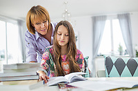 Mother assisting daughter in doing homework at table
