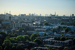 © Licensed to London News Pictures. 14/06/2017. London, UK. A view over the rooftops of Notting Hill in west London showing the London city skyline in the distance, including The Leadenhall Building AKA The Cheese Grater, 30 St Mary Axe AKA The Gherkin, Canary Wharf and the 20 Fenchurch Street skyscraper, AKA the Walkie Talkie Building, London Eye AKA Millennium Wheel. Photo credit: Ben Cawthra/LNP