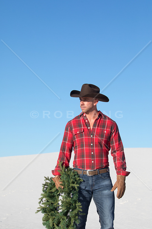 cowboy with a Christmas wreath outdoors