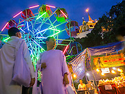 "27 NOVEMBER 2012 - BANGKOK, THAILAND:  Buddhist nuns walk past a ferris wheel spinning in front of Wat Saket during the temple fair in Bangkok. Wat Saket, popularly known as the Golden Mount or ""Phu Khao Thong,"" is one of the most popular and oldest Buddhist temples in Bangkok. It dates to the Ayutthaya period (roughly 1350-1767 AD) and was renovated extensively when the Siamese fled Ayutthaya and established their new capitol in Bangkok. The temple holds an annual fair in November, the week of the full moon. It's one of the most popular temple fairs in Bangkok. The fair draws people from across Bangkok and spills out in the streets around the temple.   PHOTO BY JACK KURTZ"