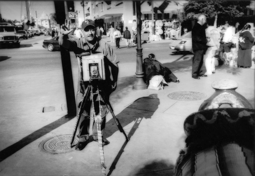 Photographer with an ancient view camera makes portrait along Tijuana's famous Avenida Revolucion immediately adjacent to Zona Norte, Tijuana, Mexico.