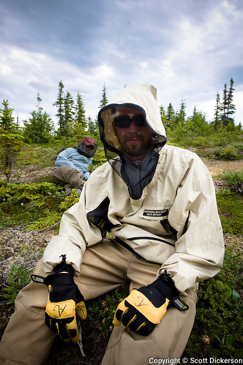 Anders  Gustafson and Tim Sohn wear mosquito nets while resting on the banks of the Koktuli River in Bristol Bay, Alaska.