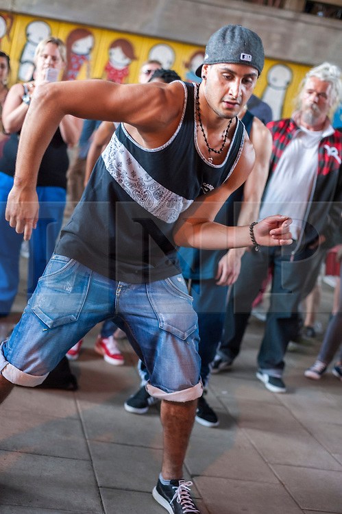 """(c)Licensed to London News Pictures. 27/07/2014. London. England. Dancers and audience at The Bridge, an annual event celebrating hip-hop culture organised by Scanners Inc under Hungerford Bridge at London's South Bank. Kate Scanlan of Scanners Inc says """"It's about all ages and nationalities having fun and showing what hip hop culture can be. People here have known each other for 40 years and now their kids are dancing, that makes me really happy to facilitate it. Next year we are planning to run it 4 times, each with different themes."""" Photo credit Carole Edrich/LNP"""