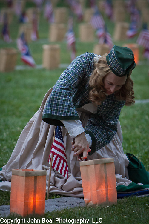 "Civilian reenactors, Lisa Donnelly lights luminarias at the Soldiers National Cemetery, during the Sesquicentennial Anniversary of the Battle of Gettysburg, Pennsylvania on Sunday, June 30, 2013.   Following ""A New Birth of Freedom"" program at Meade's Headquarters, a procession by candlelight was led to the cemetery. John Boal photography"