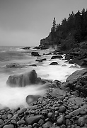The granite rocks of Otter Cliffs in Acadia National Park are battered by a fall storm in this monochromatic study.
