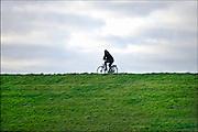 Nederland, the Netherlands, Nijmegen, 10-12-2015Een eenzme fietser op de dijk langs de rivier de Waal.FOTO: FLIP FRANSSEN/ HH