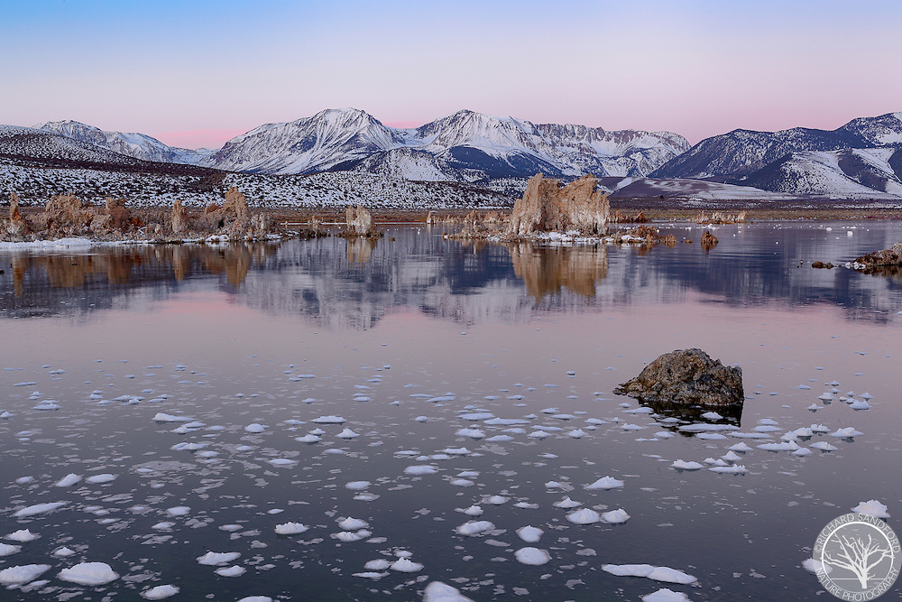 Snow-capped mountains, tufas and morning twilight reflect in Mono Lake, near Lee Vining, California.