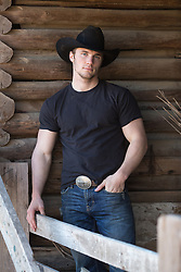 cowboy leaning against a wooden barn