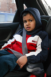 Young boy strapped in baby seat in the back of car,