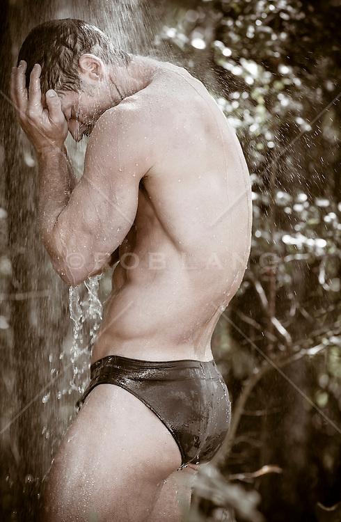 man in bikini briefs under an outdoor shower