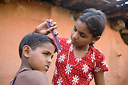 .Pooja, 14, a student from the village of Pathpuri, Hoshangabad, Madhya Pradesh, India, taking part to the children's journal, a project launched by Dalit Sangh, an NGO which has been working for the uplift of scheduled castes for the past 22 years, is taking care of her younger brother Narendra Kumar, 9, in their home. Dalit Sangh is working in collaboration with Unicef India to promote education and awareness within backward communities. .