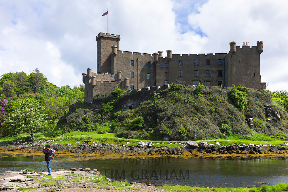 Tourist taking photographs at highland fortress Dunvegan Castle, the Highlands ancestral home of the MacLeod clan, and loch on the Isle of Skye, Scotland