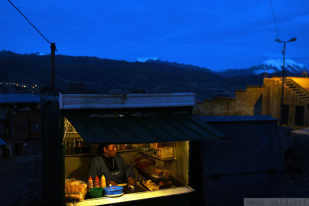 A woman sells hot dogs as the night closes in by the city of La Paz, in the background on October 2007.