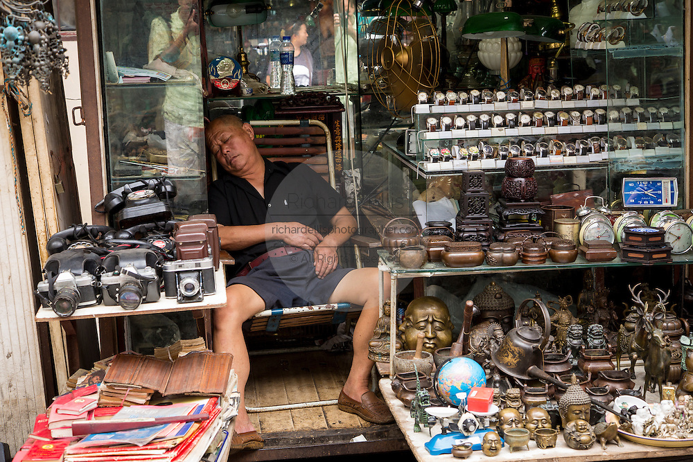 Seller asleep at Dongtai Lu antique market in Shanghai, China