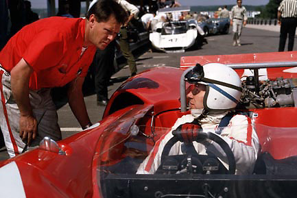 "John Surtees, reigning Can-Am champion of the year before, in new Lola T70 at Elkhart Lake's Road America, the opening round of the 1967 series. Bending over the cockpit is mechanic Malcolm Malone, known as ""Mac,"" who been Surtees' winning crew chief in '66 (Malone's ID confirmed by his sister, Kath, in February 2015). PHOTO BY Pete Lyons 1967 / www.petelyons.com"