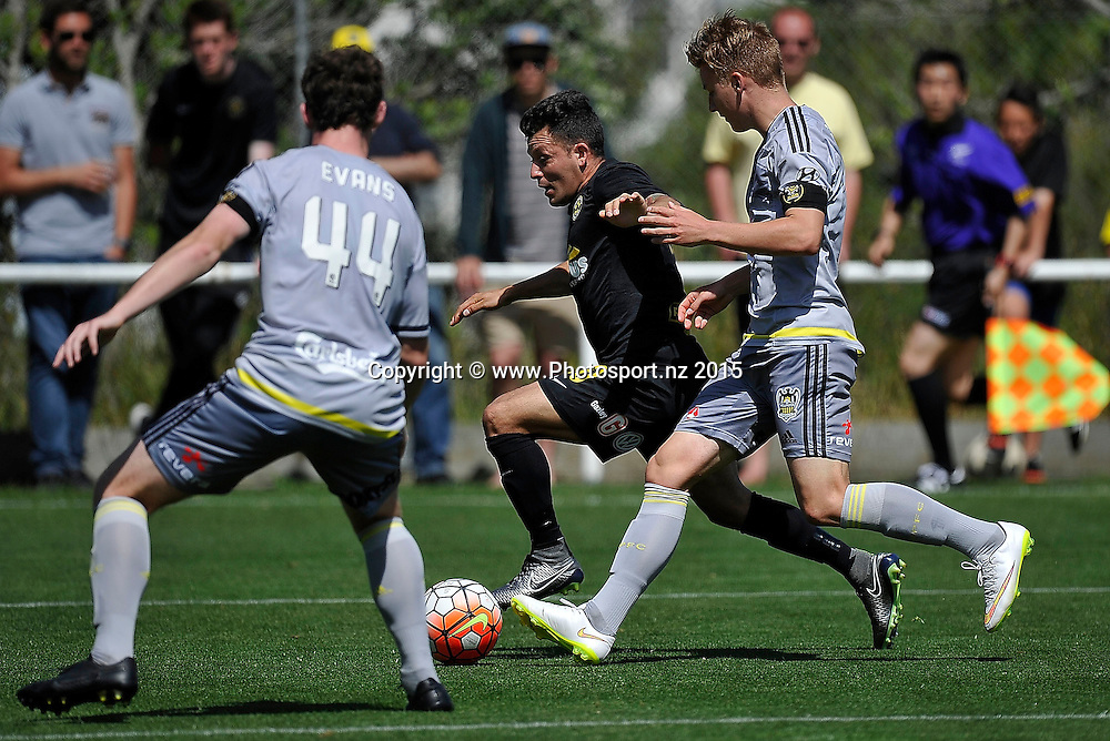 Luis Corrales (C of Team Wellington dribbles the ball with James McGarry (R and Louis Evans (L) of the Phoenix Reserves during the ASB Premiere  - Team Wellington vs Phoenix football match at David Farrington Park in Wellington on Sunday the 20th of December 2015. Copyright Photo by Marty Melville / www.Photosport.nz