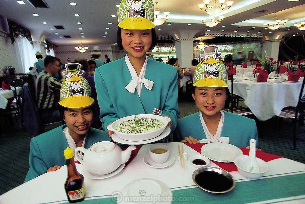 Waitresses at the Roasted Goose restaurant outside Kunming present one of the establishment's specialties, an ant and chicken egg casserole, Kunming, China. (Man Eating Bugs page 104 Top)