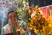Chinese religious festival in a small town. Participants in theatre in costume at a shrine in the town.
