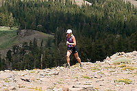 Young woman trail running through wildflowers at Kirkwood Resort. Lake Tahoe, CA